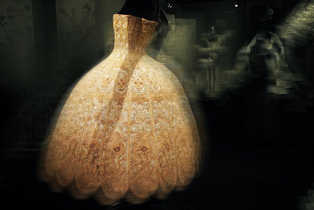 中国の宮廷衣装を思わせる刺繍を施したゴールドのブロケードは、クチュールの技巧によって球体のような構築的なシルエットへと作り変えられる