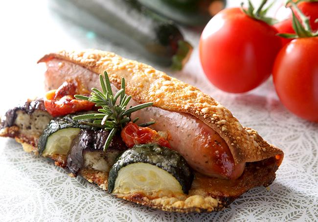 ハーブソーセージがまるごと1本と夏野菜がクリスピーなパンにはさまれた「ハーブソーセージと夏野菜」 ¥420 | ©  Joël Robuchon