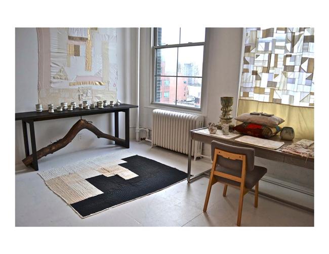 壁にかかったタペストリーWH ¥450,000 (限定数 1)、キルティングラグBK ¥150,000 (限定数 1)、黒いテーブルの上にあるカップ 各¥18,000 (限定数 5)