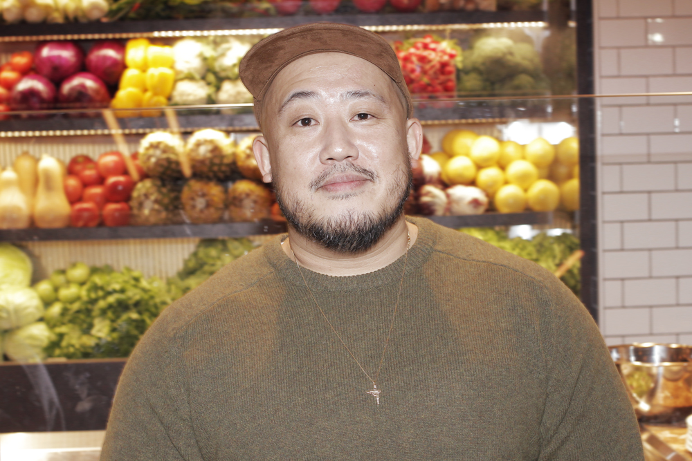CITYSHOP クリエイティブ・ディレクター吉井雄一。色とりどりの野菜を一面に並べたデリカテッセンのショーケースの前にて | © The Fashion Post