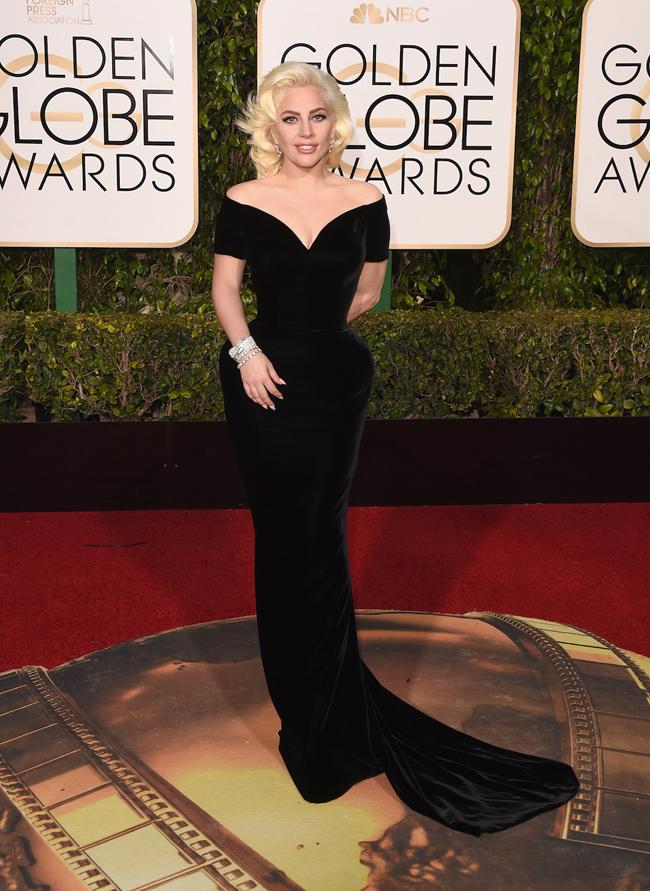 Lady Gaga (レディー・ガガ)。アワーグラスシルエットが女神を彷彿とさせるブラックドレスは Atelier Versace (アトリエ ヴェルサーチ) のもの | GettyImages