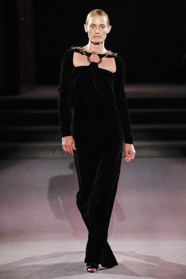 ブラックベルベット、シャープなライン、ダイナミックなゴールドのアドーンメント。彫刻のようなドレスを纏うのは、Amber Valletta (アンバー・バレッタ)