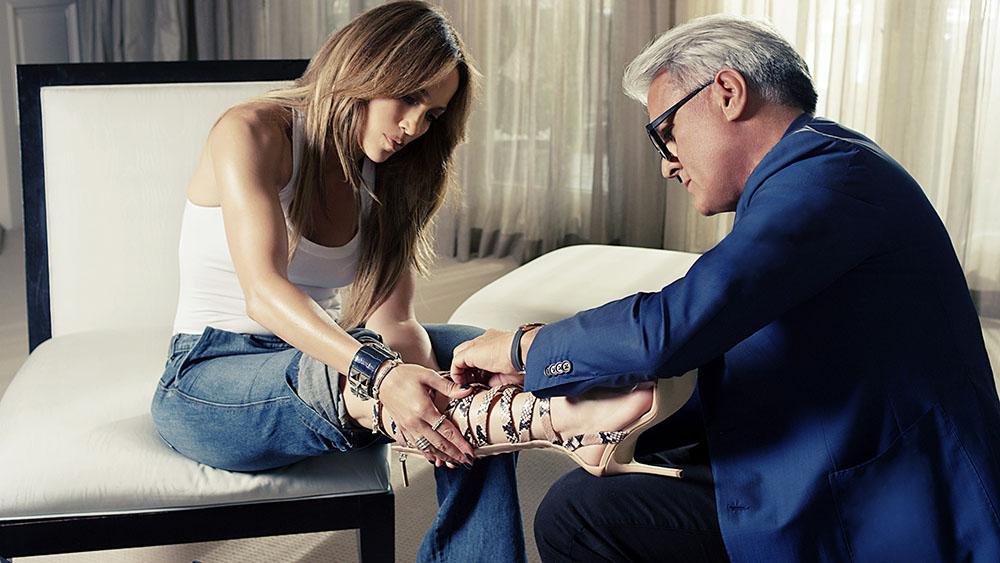 美しい靴は時に苦痛?コラボで製作したグラディエーターサンダルに足を通す Jennifer Lopez。| © Giuseppe Zanotti Design